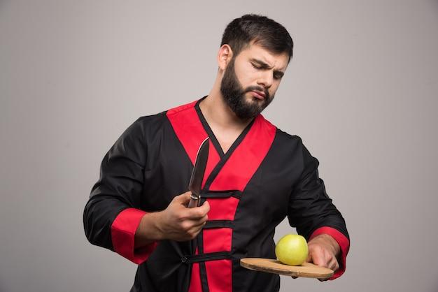 Homem sério, segurando a placa de madeira com maçã e faca.