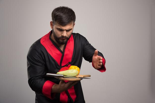 Homem sério, segurando a placa de madeira com pimenta amarela, abobrinha e faca.