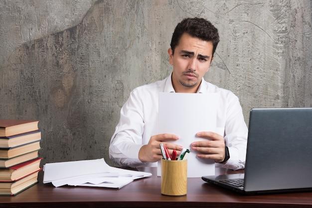 Homem sério, segurando folhas de papel e sentado à mesa. foto de alta qualidade