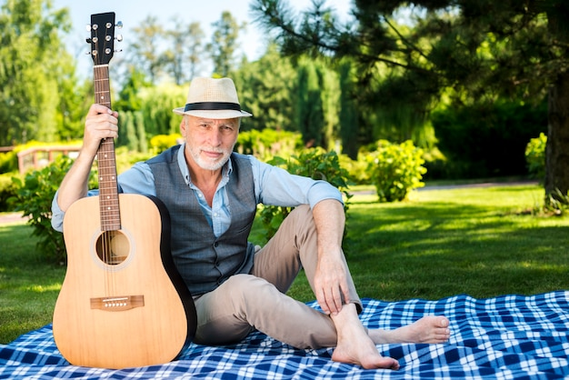 Homem sério, segurando uma guitarra na natureza