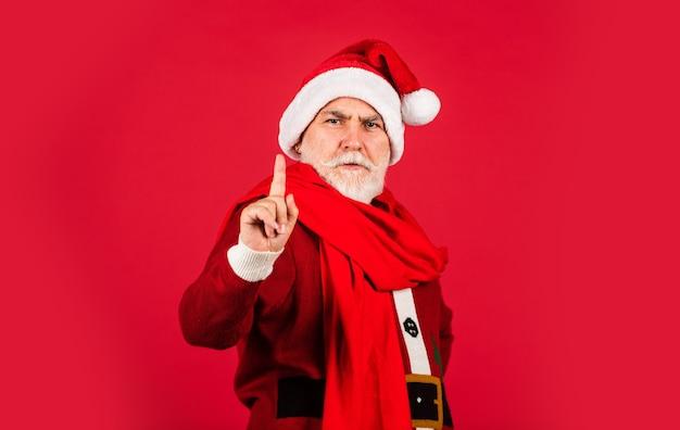 Homem sério sênior com fantasia de papai noel. feliz ano novo de 2021. feliz natal. barbudo santa no lenço sobre fundo vermelho. presentes de natal e hora de compras de presentes. alegria do feriado de inverno.