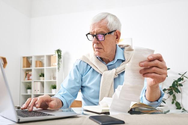 Homem sério sênior de óculos segurando contas de pagamento enquanto está sentado à mesa e inserindo dados no laptop em casa