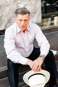 Homem sério, sentado na calçada e segurando um chapéu nas mãos, olhando para a câmera.