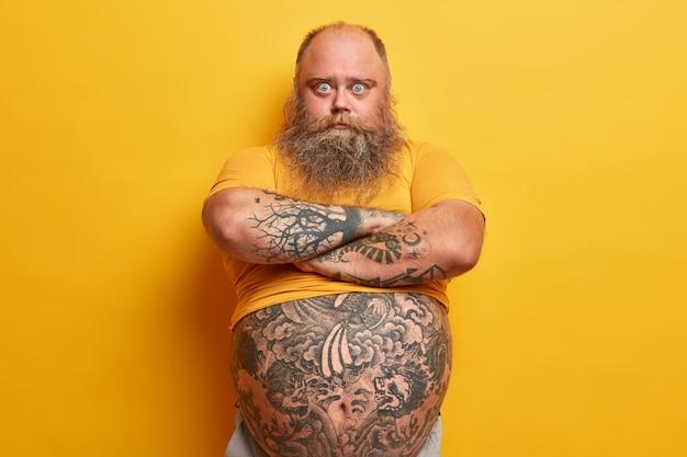 Homem sério surpreso de olhos azuis com barba espessa, mantém os braços cruzados, ouve a explicação da esposa, sente ciúme, tem barriga grande, excesso de peso por causa de alimentação inadequada, isolado na parede amarela
