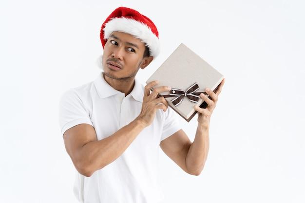 Homem sério, tentando adivinhar o que está dentro da caixa de presente de natal