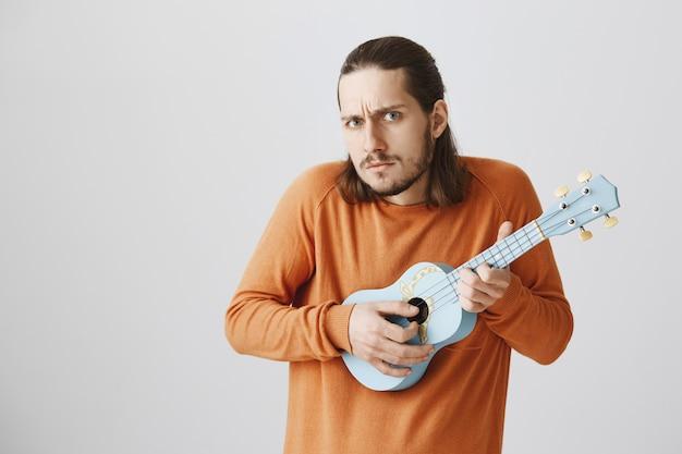 Homem sério tocando ukulele com cara de suspeita