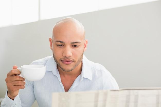 Homem sério, tomando café durante a leitura de jornal