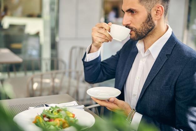 Homem sério tomando café, pensando profundamente enquanto espera por seu parceiro de negócios