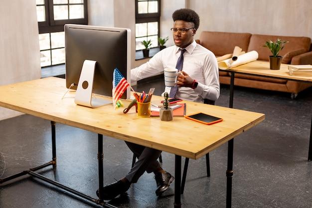Homem sério tomando chá no trabalho enquanto está muito ocupado