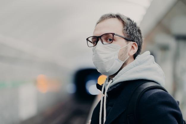 Homem sério usa máscara médica contra doenças transmissíveis, viaja no metrô, corre perigo de transporte público, tenta trabalhar em um metrô lotado. coronavírus, covid-19
