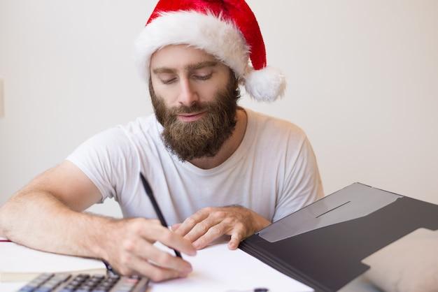 Homem sério, usando chapéu de papai noel e trabalhando com documentos