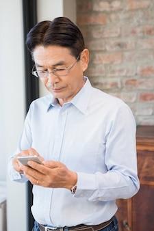 Homem sério, usando smartphone em pé em casa