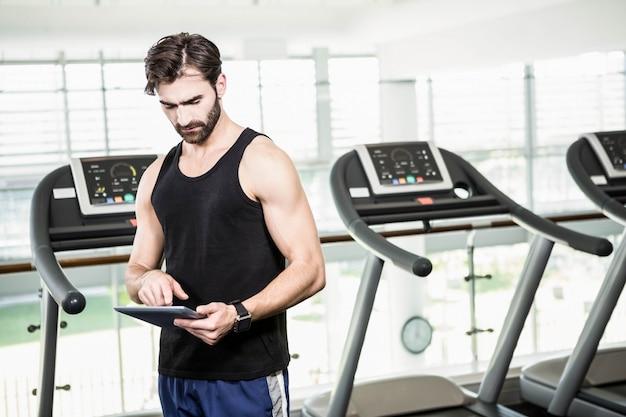Homem sério usando tablet contra esteiras no ginásio
