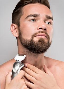 Homem sério usando um barbeador elétrico