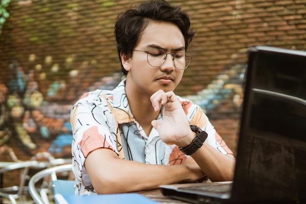 Homem sério, usando um laptop