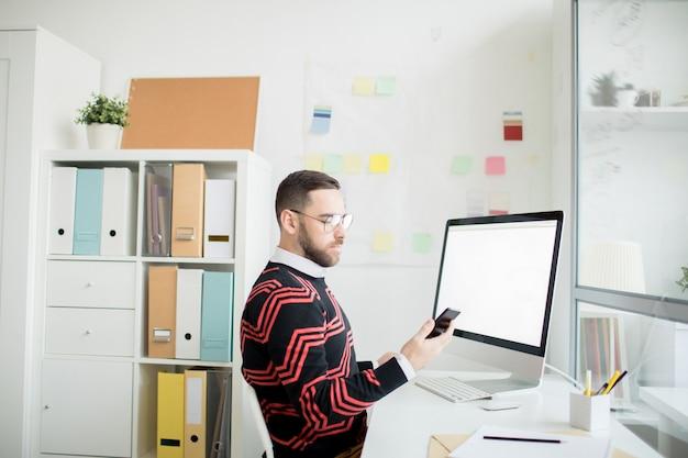 Homem sério, verificando a mensagem no telefone no escritório