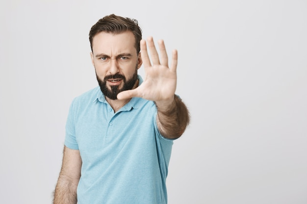 Homem sério zangado estende a mão, mostra gesto de parar, restrição