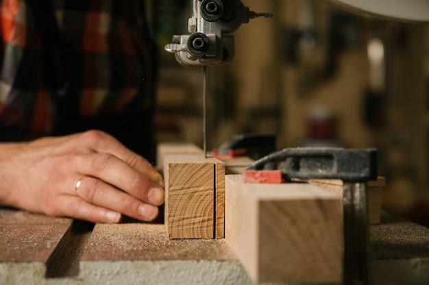 Homem serrar uma tábua de madeira em uma serra de fita, close-up