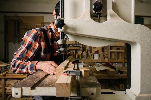 Homem serrar uma tábua de madeira em uma serra de fita
