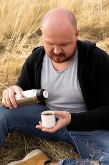 Homem serve chá em uma xícara da garrafa térmica ao ar livre