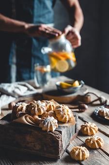 Homem serve chá quente com fatias de toranja fresca na madeira