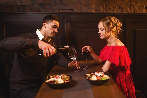 Homem serve vinho em uma taça, casal no restaurante