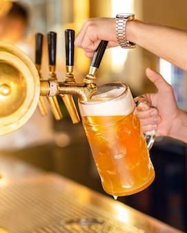 Homem servindo, enchendo copo de cerveja, caneca