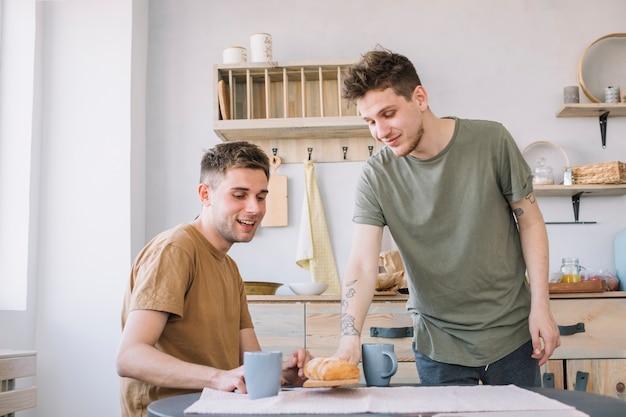 Homem servindo pão e café na mesa de madeira