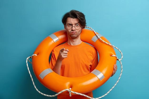 Homem severo desagradado sério que o salvador aponta para você e avisa sobre perigo na água, posa com bóia salva-vidas, trabalha em praia tropical, vestido com camiseta laranja, pronto para a salvação de pessoa que está afundando