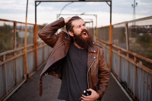 Homem severo e brutal com um longo bigode em uma jaqueta de couro marrom segura seu cabelo e grita contra o fundo de uma ferrovia