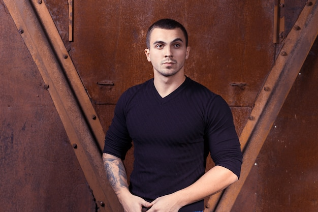 Homem sexual jovem brutal na camisola preta