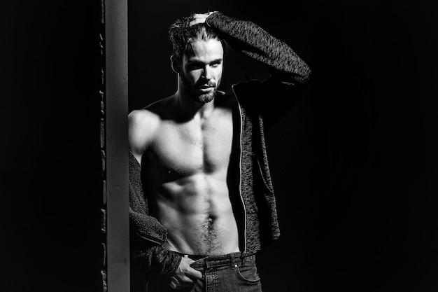 Homem sexy com torso nu musculoso em estúdio em fundo preto e parede de tijolos, copie o espaço