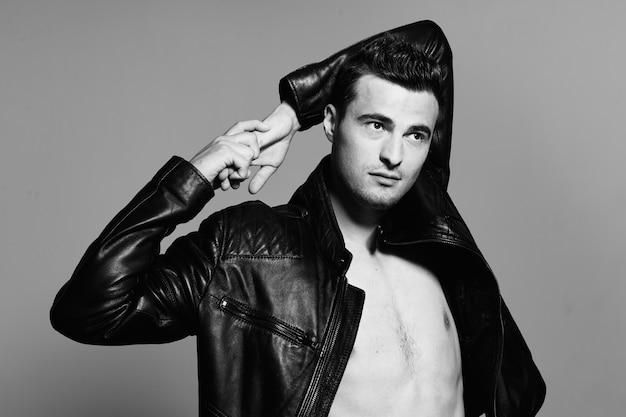 Homem sexy em uma jaqueta de couro com um torso nu.