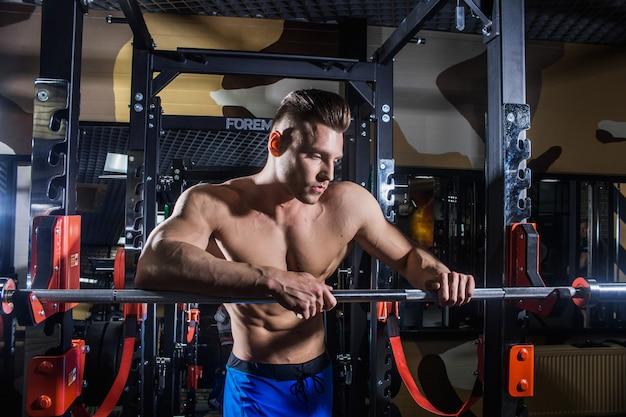 Homem sexy na academia com halteres. desportivo homem com grandes músculos e uma ampla volta treina no ginásio