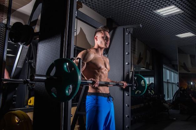 Homem sexy na academia com halteres. desportivo homem com grandes músculos
