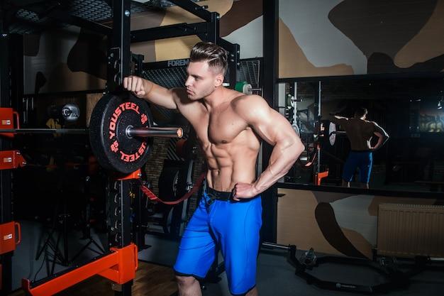 Homem sexy no ginásio com halteres. homem desportivo