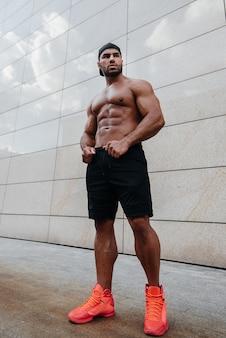 Homem sexy, posando de topless no sol quente. ginástica. estilo de vida.