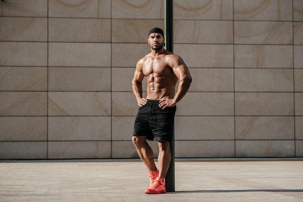 Homem sexy, posando de topless no sol quente. ginástica. estilo de vida