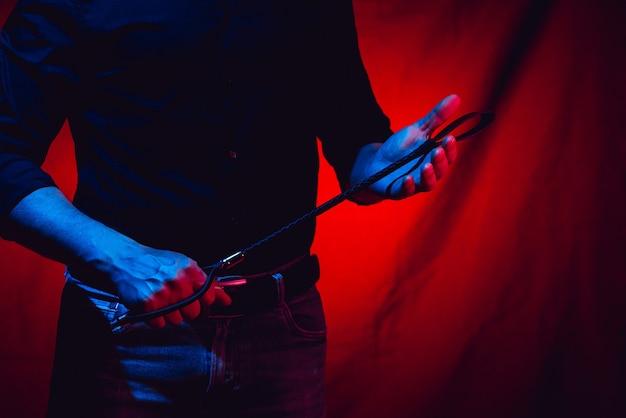 Homem sexy segurando um chicote bdsm em um fundo vermelho