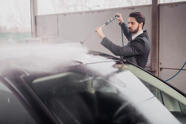 Homem sharp-vestido que lava seu carro na lavagem de carros