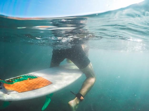 Homem, shorts, sentando, surfboard, azul, água