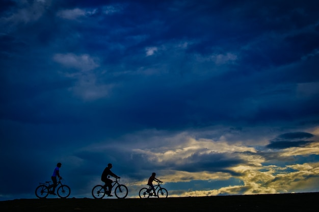 Homem silhueta pedalando em parque público ao pôr do sol