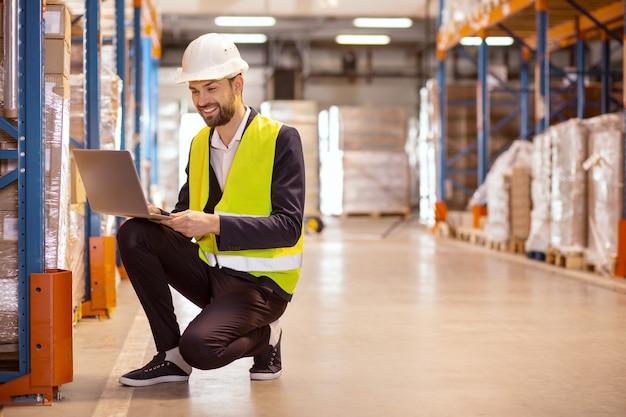 Homem simpático e alegre olhando para a tela do laptop enquanto trabalha no depósito