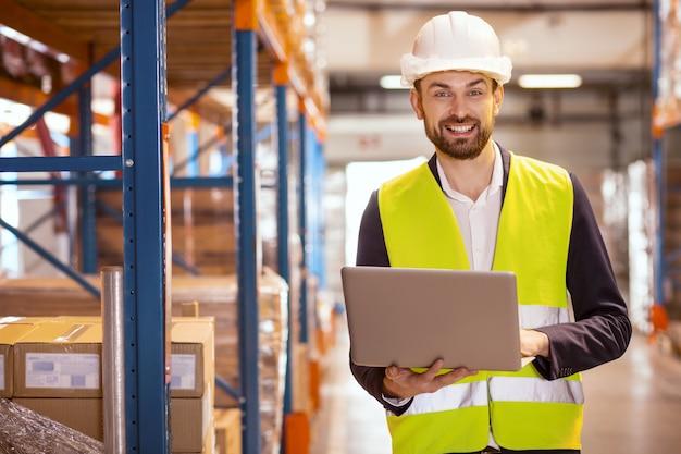 Homem simpático e alegre sorrindo enquanto lida com o sistema de logística no armazém