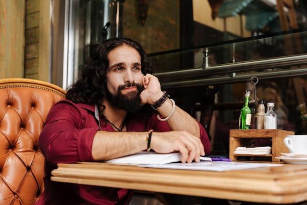 Homem simpático e atencioso no café pensando em seu trabalho