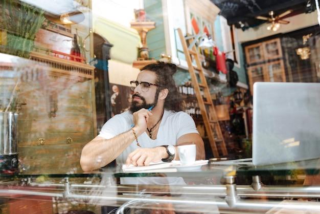 Homem simpático e atencioso segurando uma caneta enquanto faz anotações no café