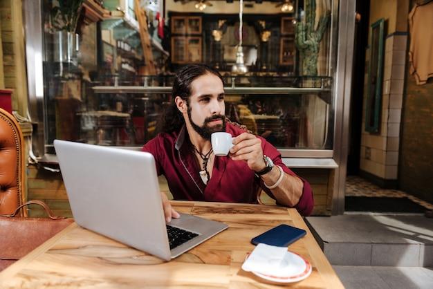 Homem simpático e bonito segurando uma xícara com café expresso enquanto trabalha no laptop