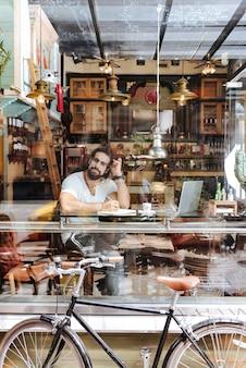 Homem simpático e criativo olhando pela janela enquanto faz anotações