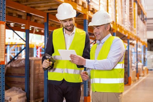 Homem simpático e positivo segurando um tablet enquanto o mostra a seu subordinado
