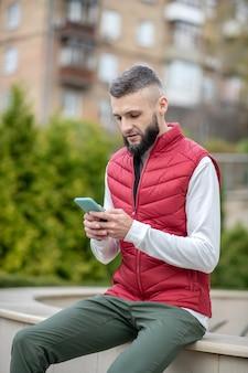 Homem simpático e sério segurando seu smartphone enquanto verifica suas mensagens